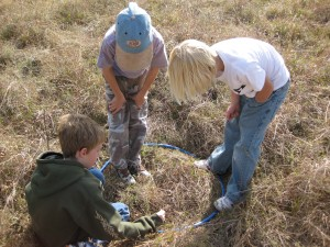 A hula hoop becomes a place to look for plant and animal species at Sneed Prairie